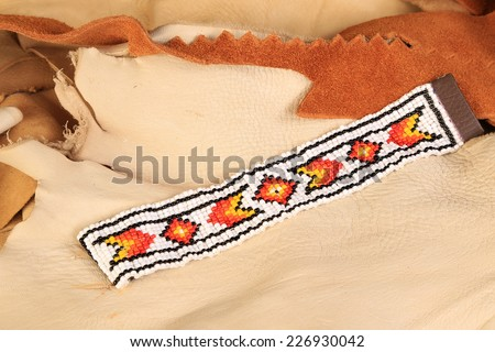 Native American pattern in black, orange, yellow and white beaded bracelet on scraps of leather and rawhide. - stock photo