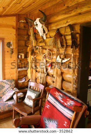 Native American & south western art and artifacts hang on log cabin wall. - stock photo