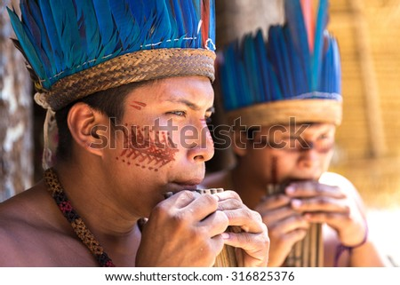 Native Brazilian guys playing wooden flute at an indigenous tribe in the Amazon - stock photo