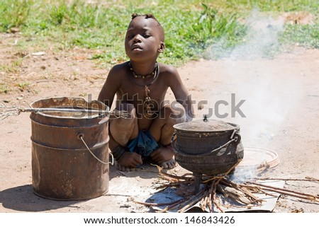 Native Himba boy cooking lunch - stock photo