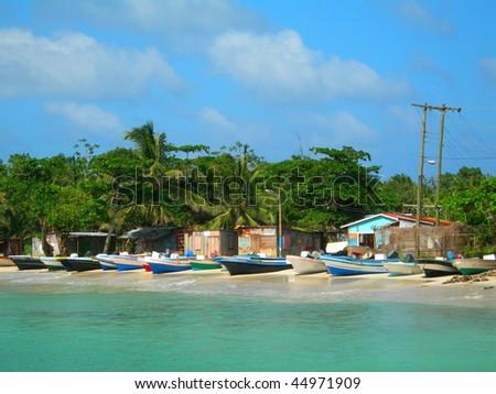 native panga fishing boats on beach with native zinc houses brig bay corn island nicaragua central america - stock photo