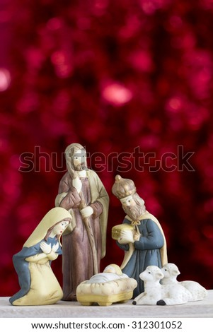 Nativity Scene with Baby Jesus, Mary, Joseph, Sheep and a Wise Man on a Red Background with Copy Space Vertical  - stock photo
