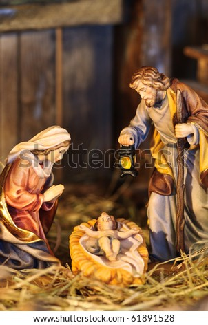 nativity scene with hand-colored figures made out of wood - stock photo
