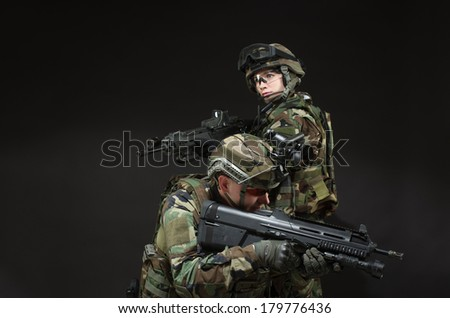 NATO soldier in full gear. Military man and woman over black background. - stock photo