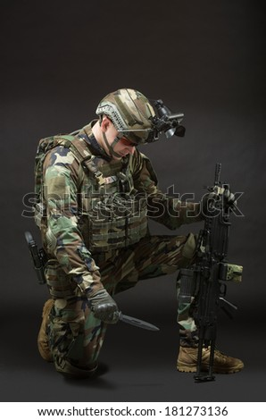 NATO soldier in full gear. Military man over black background.