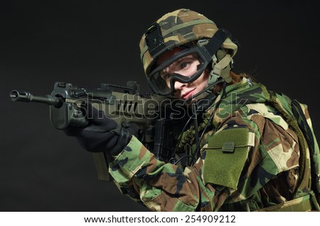 NATO soldier in full gear. Military woman over black background. - stock photo