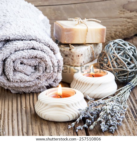 Natura Spa and Wellness with burning Candles, Lavender Bouquet and Homemade Soaps on Wooden Background - stock photo