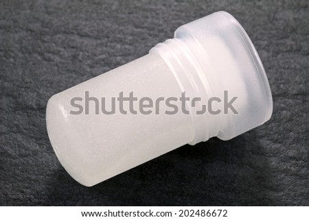 Natural alum crystal underarm deodorant on black background - stock photo
