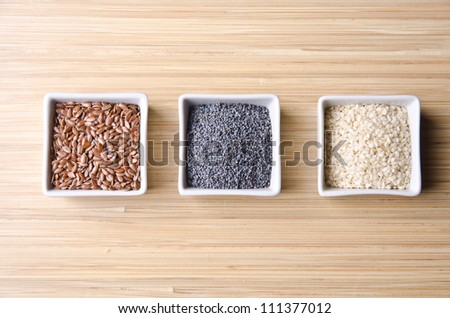Natural and healthy flax, poppy and sesame seeds in little white square bowls. - stock photo
