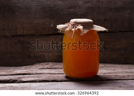 Natural apple juice on old wooden boards. Ecoproduct on wooden shelf. Canning juice in the cellar. - stock photo