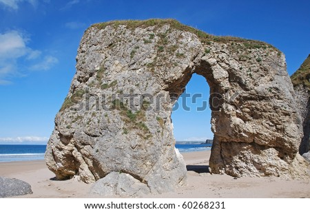 Natural arch of limestone and a blue sky on the White Rocks Beach near Portrush in Antrim Northern Ireland - stock photo
