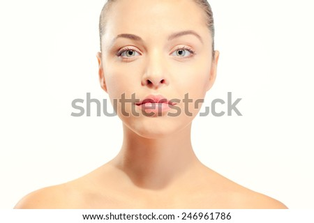 Natural as she is. Portrait of beautiful caucasian young shirtless woman looking at camera while standing against white background - stock photo