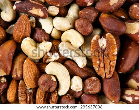 Natural background texture made from mixed kinds of nuts - pecans, hazelnuts, walnuts, cashews, almonds, pine nuts, pistachios. - stock photo