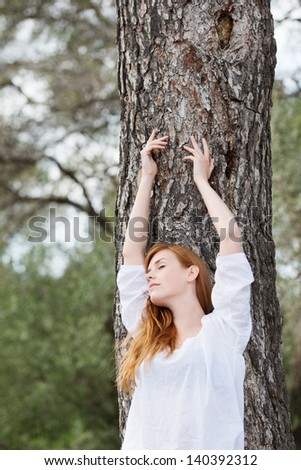 Natural beauty - a beautiful young woman relaxes against a tree trunk with her arms raised against the bark and her eyes closed in pleasure and appreciation, low angle portrait - stock photo