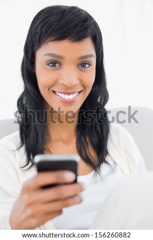 Natural black haired woman in white clothes holding a mobile phone in a living room - stock photo