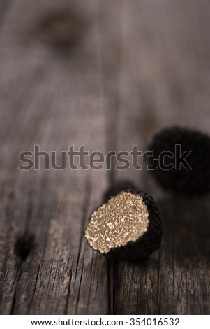 Natural black truffle on old wood table - stock photo