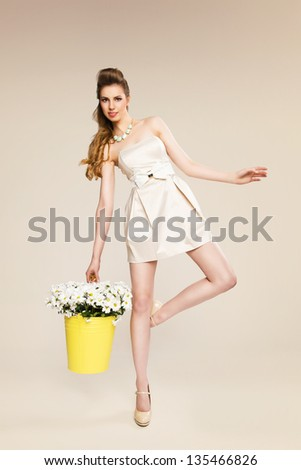 Natural blonde beauty wearing trendy dress posing with basket full of flowers on beige background - stock photo