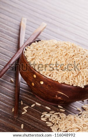 Natural brown rice background. Raw uncooked rice in wooden bowl with chopsticks on brown background. Culinary rice eating. - stock photo