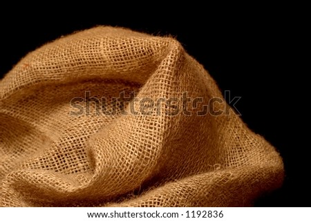 Natural burlap on black background - stock photo