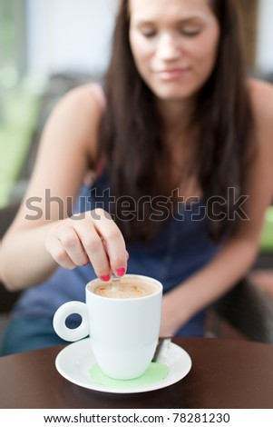 Natural/candid looking young woman stirring sugar in coffee. In an open air cafe. Selective focus on the coffee mug. - stock photo