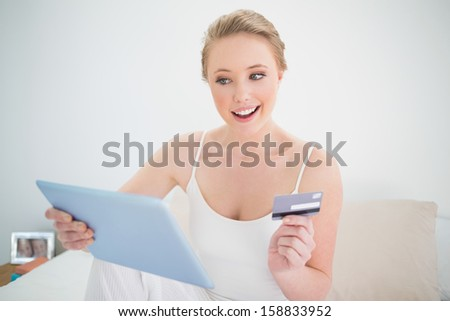 Natural cheerful blonde holding tablet and credit card in bright bedroom