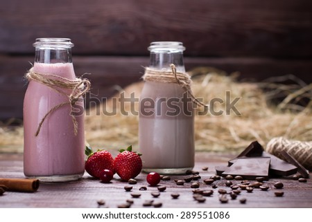 Natural chocolate and strawberry milkshakes. Chocolate, coffee beans and berries on a wooden background. - stock photo