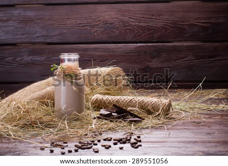 Natural chocolate milkshake is in the hay. Chocolate with coffee beans on a wooden background. - stock photo