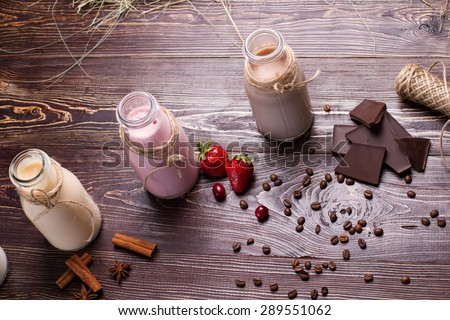 Natural chocolate, vanilla and strawberry milkshakes. Chocolate, cinnamon, coffee beans and berries on a wooden background. - stock photo