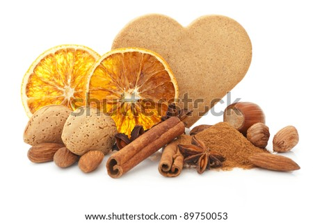 Natural christmas still life with heart shaped gingerbread cookie, orange, various nuts, cinnamon, anise and spices. Brown and orange natural xmas. - stock photo