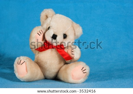 Natural colored teddy bear on a blue blanket. He has a red ribbon around his neck.  He is sitting on the blanket and has one arm raised - stock photo