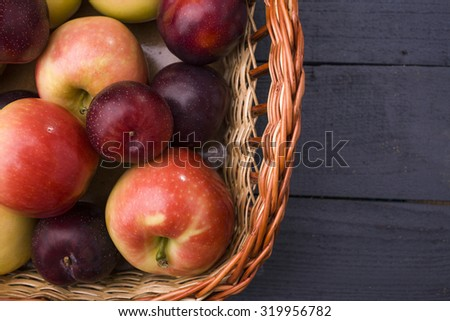 Natural colorful background of many fresh tasty ripe clear fruits of yellow red apple and purple plum lying in heap in straw basket on wooden backdrop, horizontal picture - stock photo