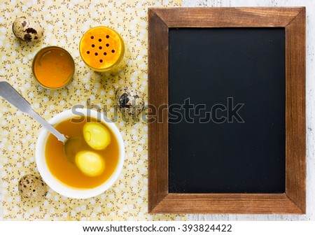 Natural coloring Easter eggs with turmeric powder in yellow color blank space for text on chalkboard top view - stock photo