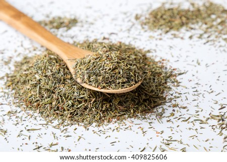 natural dried aromatic thyme on white table with spoon - stock photo