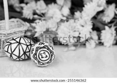 Natural eggs with free hand sketch patterns with floral background for Easter. Black and white image. Shallow Depth of field. - stock photo