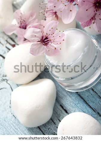 natural facial cream with beauty  cherry blossoms on wooden background - stock photo
