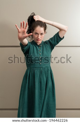 Natural female model poiting her hand to the camera white grasping her hair - stock photo