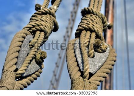 Natural fiber ropes and wooden tackle blocks - stock photo
