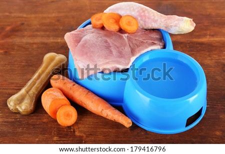 Natural food for pets and water in plastic bowls on wooden table close-up - stock photo