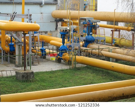 Natural gas station with yellow pipes at power plant - stock photo