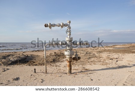 Natural gas wellheads in a plowed cornfield. - stock photo