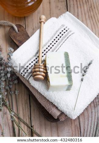 Natural goat milk, honey and lavender soap with towels, homemade spa setting - stock photo