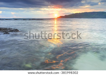 Natural green moss at beach rock with cloudy sunset background - stock photo