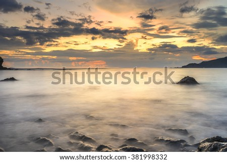 Natural green moss at beach rock with sunset moment background. Focused at foreground. - stock photo