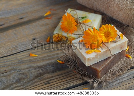 Natural handmade soap with calendula (pot marigold) on rustic wooden background
