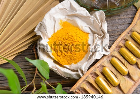 Natural herbal tumeric capsules with fresh herb leaves and dry curcumin in paper - stock photo