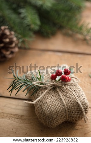 Natural holiday wrapped gift with holly berries - stock photo