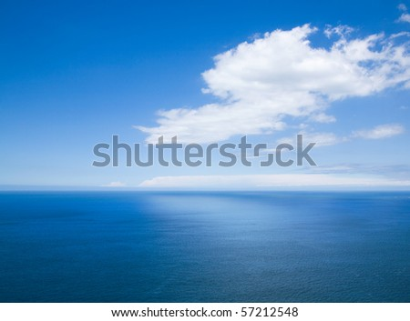 natural horizontal background - view over the ocean far below; white cloud and its reflection