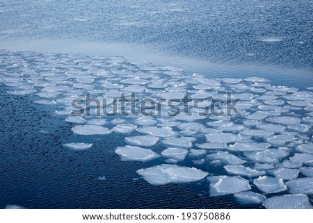 Natural ice blocks breaking up against shore and sea ice during freezing winter weather. Fast ice. - stock photo