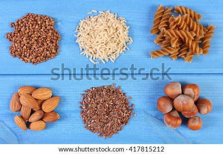 Natural ingredients and products containing magnesium and dietary fiber, healthy food and nutrition, wholemeal pasta, buckwheat, almonds, brown rice, hazelnut, linseed - stock photo