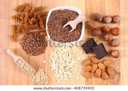 Natural ingredients and products containing magnesium and dietary fiber, healthy food, wholemeal pasta, buckwheat, brown rice, linseed, oatmeal, almonds, chocolate, hazelnut - stock photo